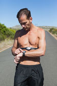 Athletic man on open road with monitor around chest — Foto Stock