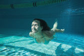 Pretty brunette smiling and swimming underwater — Стоковое фото