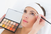 Hand applying eyeshadow to beautiful woman — Stockfoto