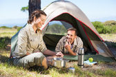 Couple cooking on camping stove outside tent — Stock Photo