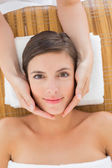 Attractive young woman receiving facial massage at spa center — Stockfoto