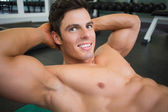 Smiling muscular man doing abdominal crunches — Stock Photo