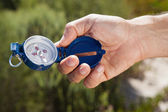 Hiker holding his compass in the countryside — Stock Photo