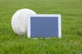Football and tablet with blank screen on pitch — 图库照片