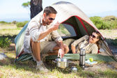 Outdoorsy couple cooking on camping stove — Stock Photo