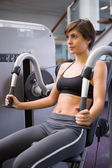 Smiling brunette using weights machine for arms — Stock Photo