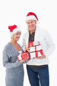 Couple d'âge mûr de fête dans des vêtements d'hiver tenant cadeaux — Photo
