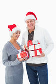 Festive mature couple in winter clothes holding gifts — Stock Photo
