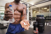 Shirtless muscular man holding vitamin pills — Stock Photo