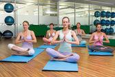 улыбаясь класс йоги в позе лотоса в фитнес-студии — Стоковое фото