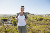 Pretty hiker smiling at camera on mountain terrain — Stock Photo