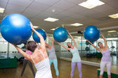 Fitness class holding up exercise balls in studio — Stock fotografie