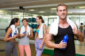 Fit man smiling at camera in busy fitness studio — Stockfoto