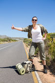 Pretty hitchhiker sticking thumb out on the road — Stock Photo