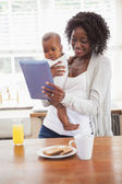 Happy mother holding baby son while using tablet pc — Stockfoto