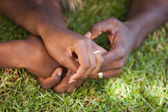 Couple holding hands on the grass — Stock Photo