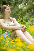 Cute young woman relaxing in field — Stock Photo