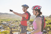 Fit cyclist couple looking ahead on mountain trail — Stock Photo