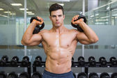 Muscular man lifting kettle bells in gym — Stock Photo