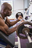 Determined muscular man lifting barbell in gym — ストック写真