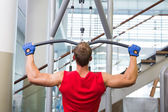 Strong man using weights machine for arms — Stock Photo