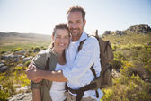 Hiking couple embracing and smiling at camera — Stok fotoğraf