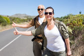 Hiking couple standing on the road with thumb out — Stock Photo