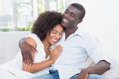 Attractive couple cuddling on the couch — Stock Photo