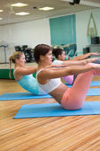Yoga class in boat position in fitness studio — Stock Photo