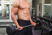 Mid section of shirtless muscular man lifting barbell — Stock Photo