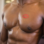 Shirtless muscular man with lipstick mark on chest — Stockfoto