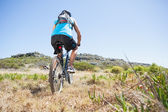 Fit cyclist riding in the countryside uphill — Foto Stock