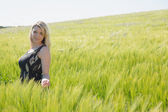 Pretty blonde in sundress standing in wheat field — Zdjęcie stockowe