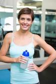 Přizpůsobit bruneta se usmívá na fotoaparát drží láhev s vodou — Stock fotografie