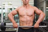 Mid section of a shirtless muscular man lifting barbell — Stock Photo