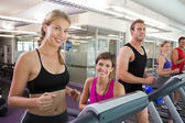 Trainer and clients smiling at camera on the treadmill — Stock Photo