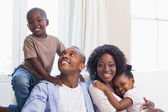 Happy family posing on the couch together — Stockfoto