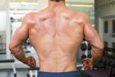 Close-up rear view of a bodybuilder in gym — Stock Photo