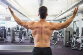 Rear view of shirtless muscular man in gym — Stock Photo