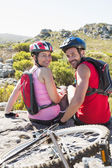 Fit cyclist couple sitting at the summit smiling at camera — Stockfoto