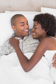 Happy couple lying in bed cuddling — Stock Photo