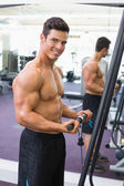 Shirtless muscular man using triceps pull down in gym — Foto Stock