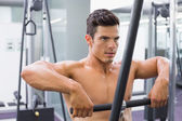 Shirtless muscular man using biceps pull up in gym — Stock Photo