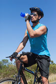 Handsome cyclist taking a break on his bike drinking water — Stock Photo