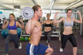 Fitness class lifting barbells together — ストック写真