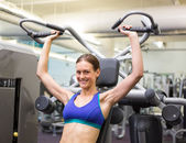 Fit happy brunette using weights machine for arms — Stock Photo