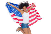 Pretty girl wrapped in american flag jumping — Foto Stock