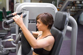 Happy brunette using weights machine for arms — Stock Photo