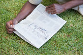 Man relaxing in his garden reading newspaper — Stock Photo