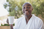 Handsome man in bathrobe having coffee outside — Stock Photo
